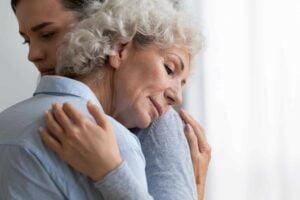 Caring granddaughter comforting, hugging sad grandmother close up