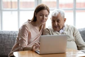 Adult daughter old father choose services via internet using computer