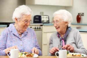 Two gray haired friends enjoying a meal together